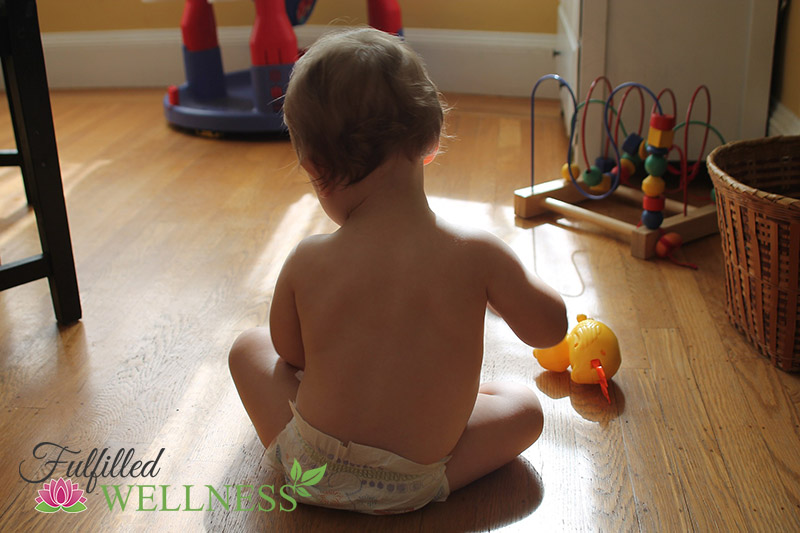 Baby playing with toys sitting on floor