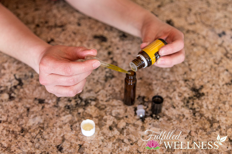 Adding essential oil and carrier oil to a roller bottle