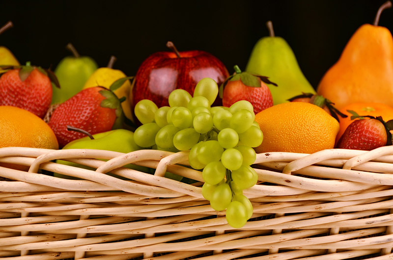 Basket of fruit such as grapes, apples, strawberries, pears and oranges
